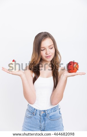 Girl holding red large apple and cupcake and thinking what to eat. Concept of dietary choices