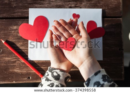 Girl holding red paper hearts. Saint Valentines Day & Love concept. - stock photo