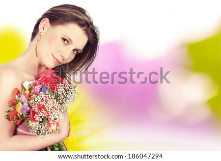 Girl holding spring flowers. Bokeh background with flowers.  - stock photo