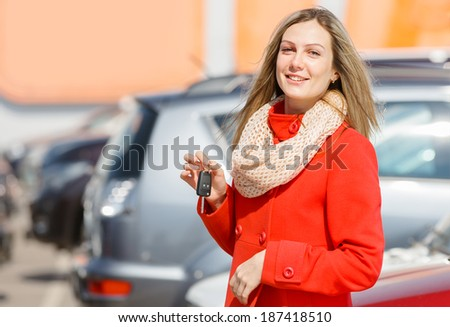 girl holding the keys in hand over cars