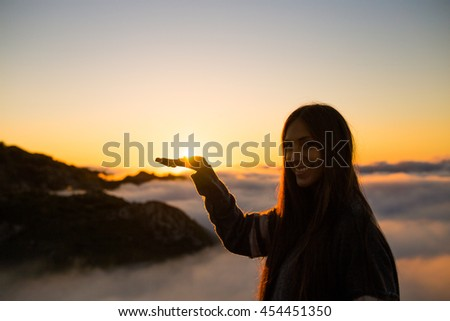 Girl holding the sun and smiling - stock photo