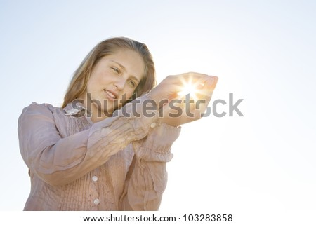 Girl holding the sun in her hands against the blue sky, smiling. - stock photo