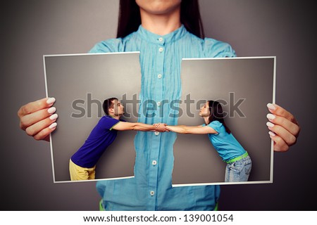 girl holding the torn photo of loving couple - stock photo
