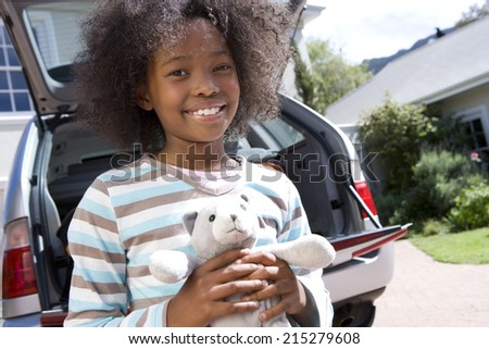 Girl (8-10) holding toy by car, smiling, portrait, low angle view