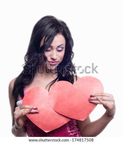 Girl holding two hearts and looks at them