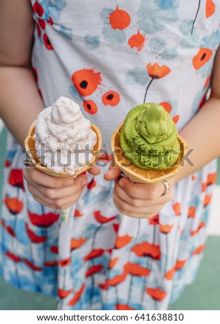 Girl holding typical Japanese ice cream with matcha and sakura petals.