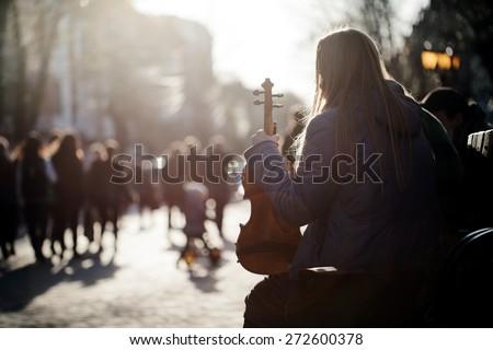 girl holding violin on a city street - stock photo
