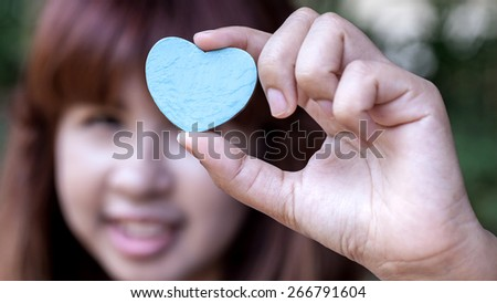 Girl holding wood shape of heart . Concept for giving love. - stock photo