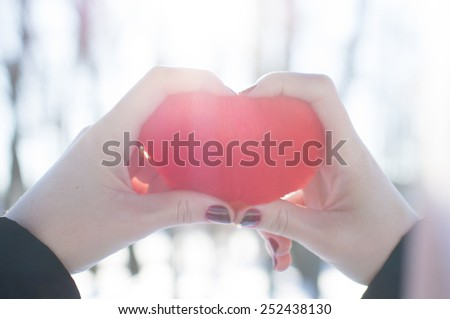 Girl holds and looks on heart in his hand. on the nature - stock photo