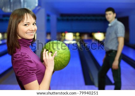 Girl holds ball for bowling and smiles, and man look at it, focus on girl