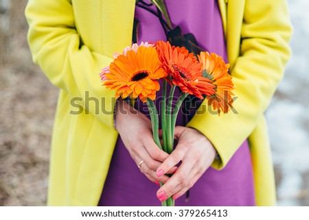 girl holds flowers, bright colors background yellow, orange, purple