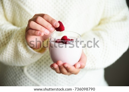 Girl holds glass of milk or yogurt, kefir with raspberries. Healthy and clean eating. Copy space. Breakfast, snack. Lifestyle concept