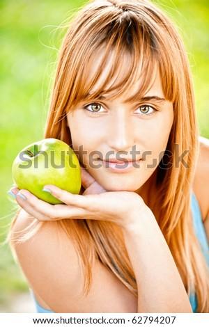 Girl holds green apple, against summer grass. - stock photo