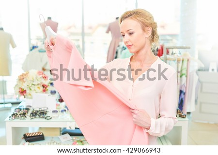 Girl holds hands and looks dress him in clothing store