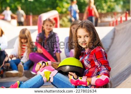 Girl holds helmet wearing in-line skates sitting - stock photo