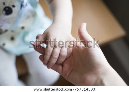 girl holds her mother's hand