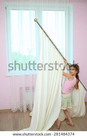 Girl holds the curtain with new draperies at the window in the room - stock photo