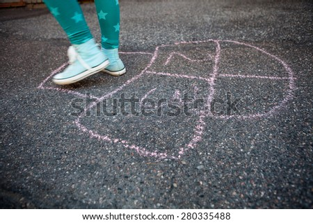 Girl hopping on hopscotch drawn to asphalt with street chalk outdoors - stock photo