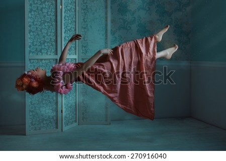 Girl hovers in the room at night. It levitates in a dream. - stock photo