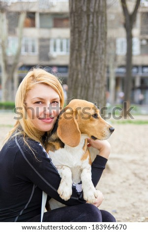 girl hugging beagle dog in park. Dogs are family - stock photo