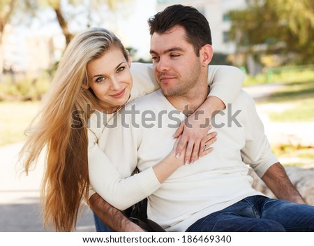 Girl hugging her boyfriend sitting on a wheelchair - stock photo