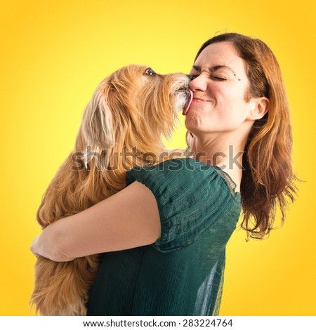 Girl hugging her dog over colorful background - stock photo