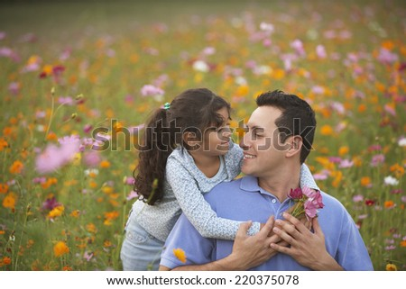 Girl hugging her father in field of flowers - stock photo