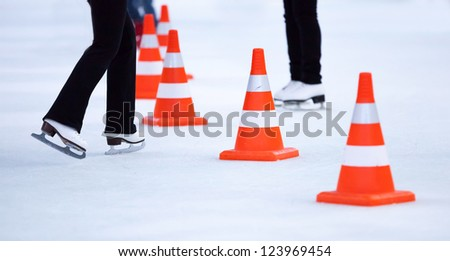 Girl ice skaters legs and red white striped cones on the ice rink - stock photo