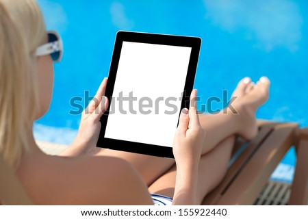 girl in a bathing suit lying on a sun lounger by the pool with a computer tablet with isolated screen - stock photo
