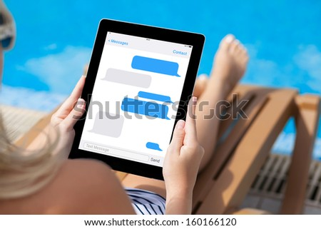 girl in a bathing suit lying on a sun lounger by the pool with a computer tablet with sms chat on a screen - stock photo