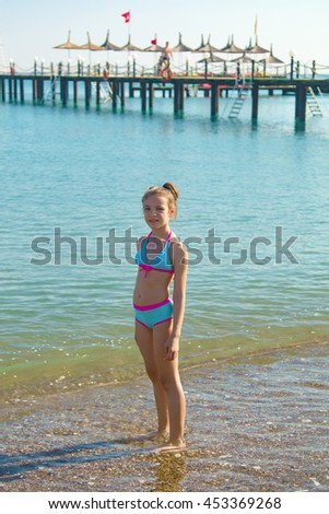 girl in a bathing suit on the beach by the sea