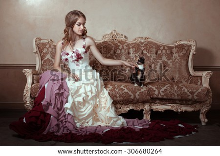 Girl in a beautiful dress with a train. She is sitting on an old couch.  - stock photo