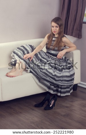 girl in a beautiful lush dress sitting on the couch - stock photo