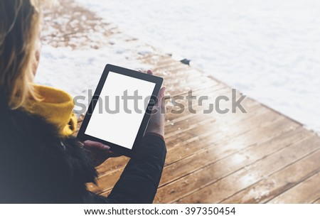 Girl in a black down jacket and yellow backpack using the tablet with a clean blank screen on a background of winter forest in the mountains with bright sun and wooden pier - stock photo