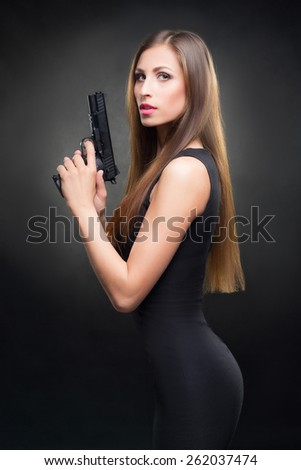 girl in a black dress holding a gun - stock photo