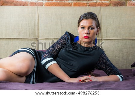 girl in a black dress sitting on a bed in a room with a brick wall in grunge style