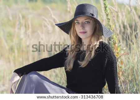 Girl in a black hat walks in the woods. Blonde in a black hat. A girl with long blond hair in a black wide-brimmed hat.