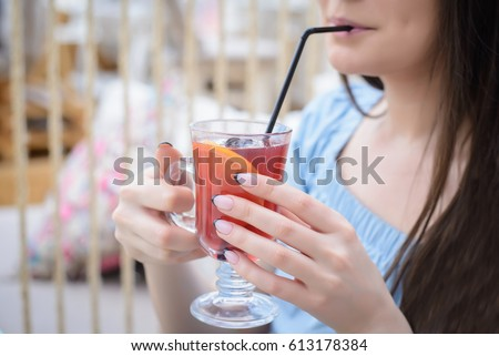 Girl in a blue blouse drinking mulled wine from a glass through a straw for a table in a cafe