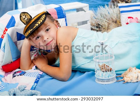 girl in a blue dress and white cap on a background seascape