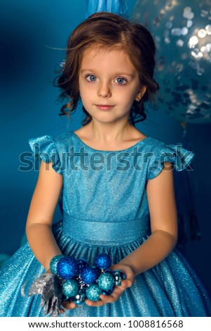 girl in a blue dress holding a blue Christmas balls