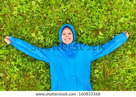 Girl in a blue raincoat lying on a meadow - stock photo