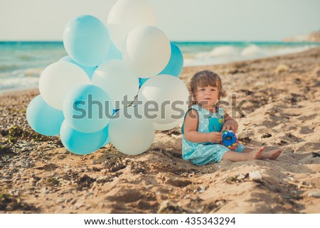 Girl in a blue suit sitting on a beach in the sand with blue balloons - stock photo