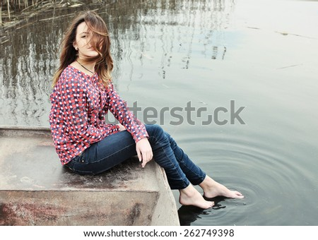 Girl in a boat on the river - stock photo