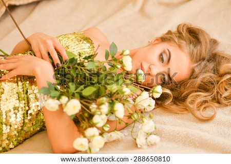 girl in a brilliant dress with a bouquet of roses