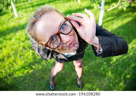 Girl in a business suit holding his hands over the rim glasses, looking strictly at frame - stock photo