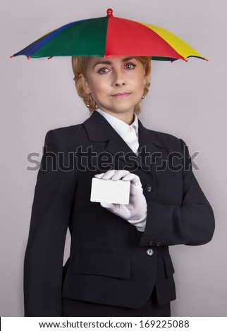 Girl in a business suit under the umbrella keeps credit card