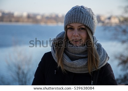 girl in a cap and scarf walking on the lake