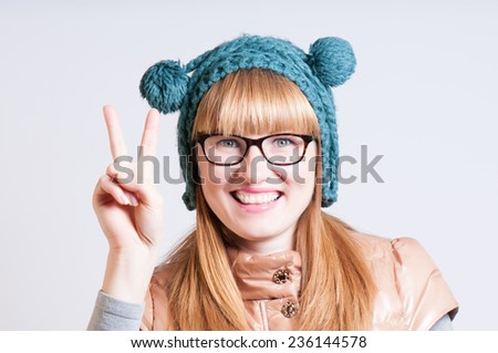 girl in a cap with a pompon shows two fingers, Victory - stock photo