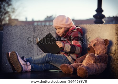 girl in a checkered coat sitting on a park bench and reading a book toy Bear. Toning, vignette