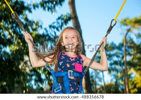 Girl in a city park on a trampoline jumping high on a background of trees and sky